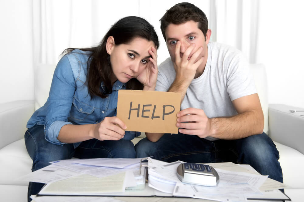 Couple in debt holding up HELP sign